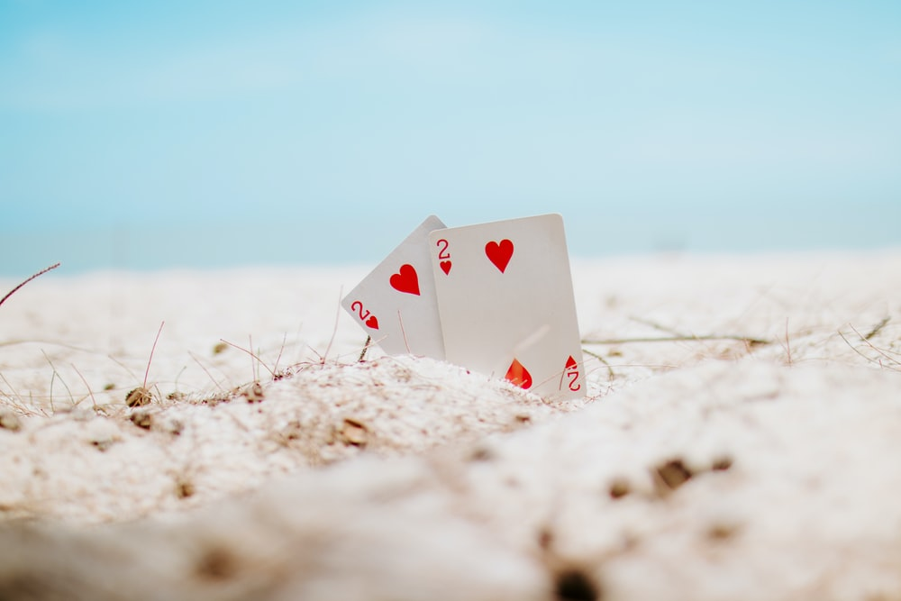 white and red heart playing card on white sand during daytime