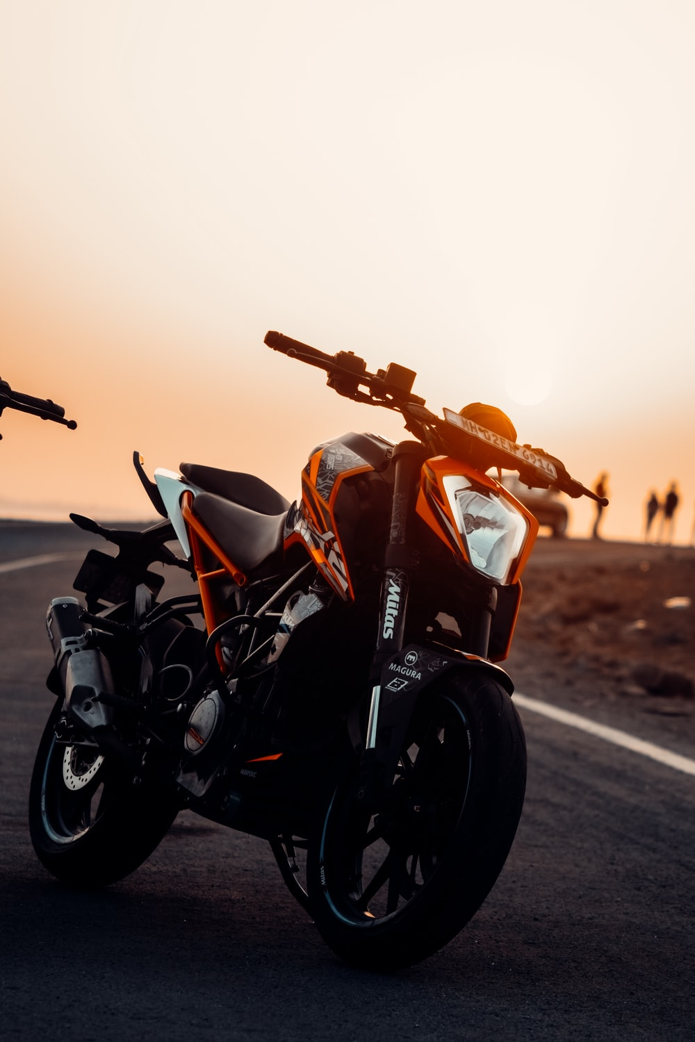 black and red motorcycle on road during sunset