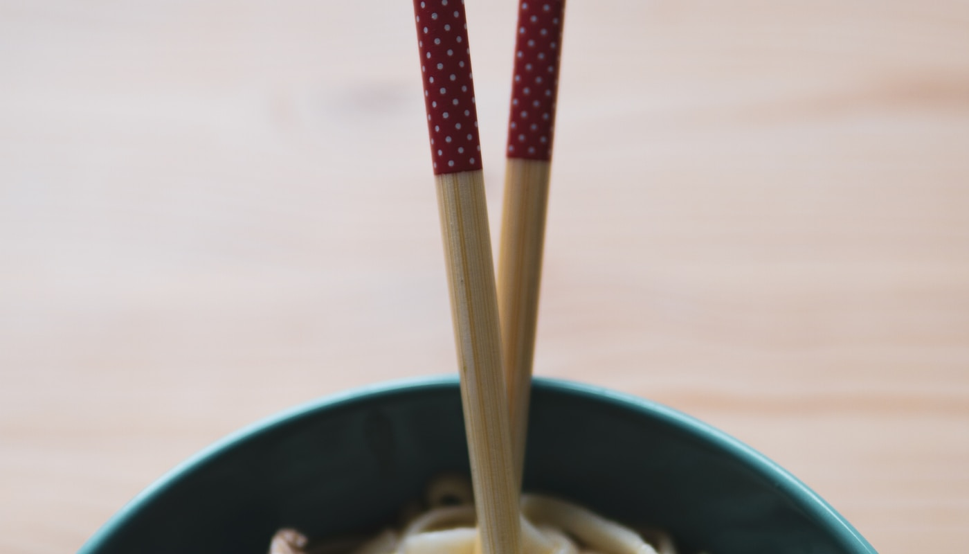 green and white ceramic bowl with brown chopsticks