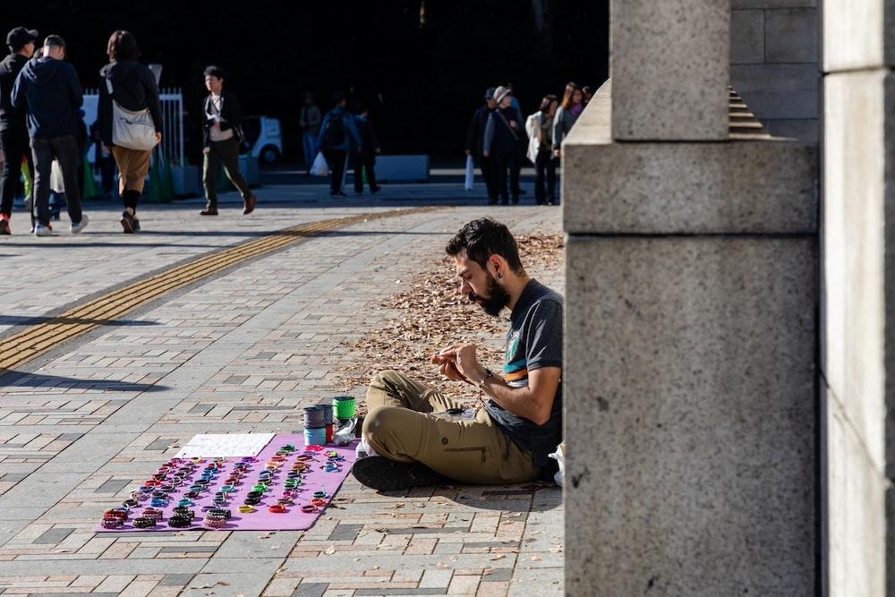 man in black t-shirt sitting on concrete bench