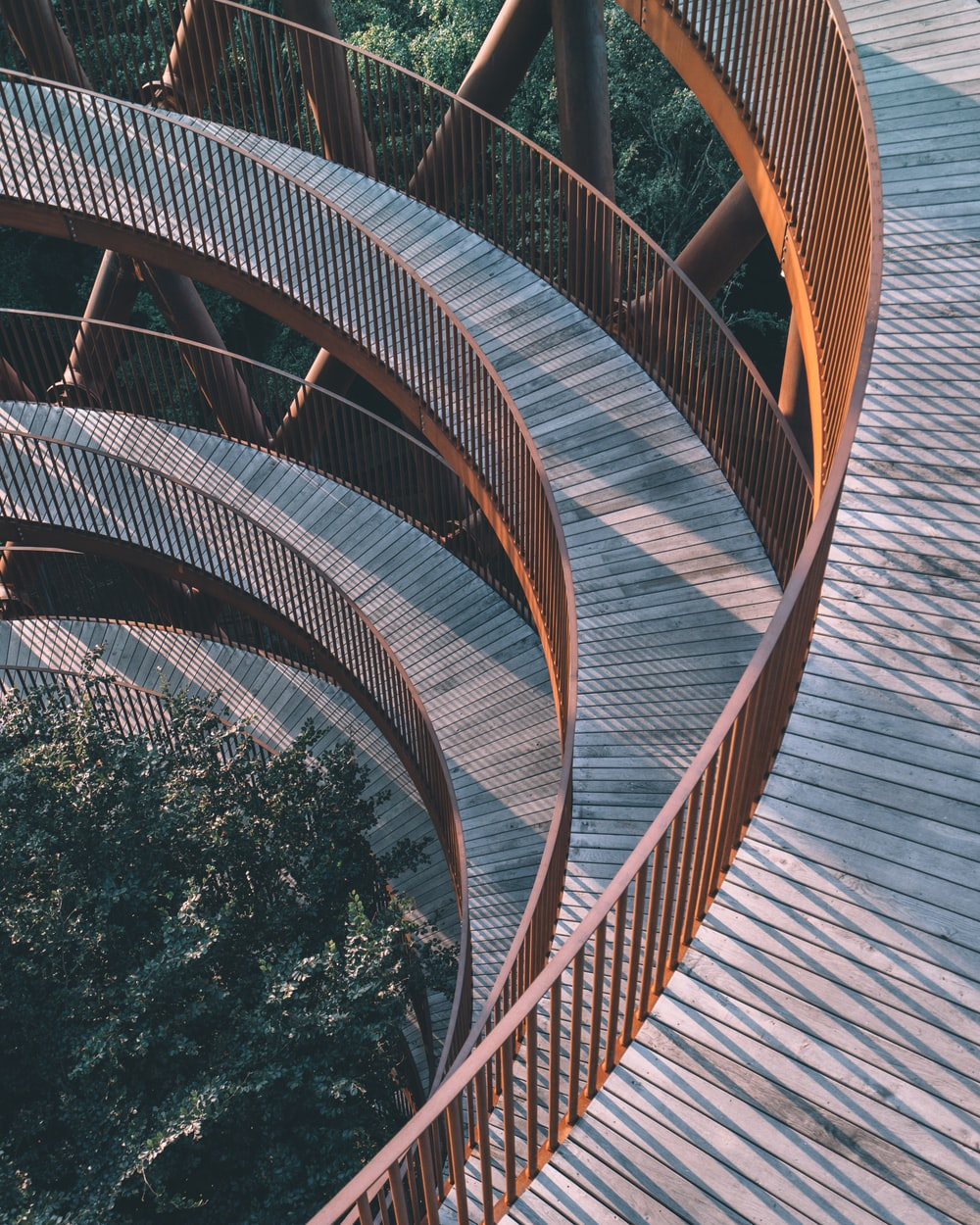 brown spiral staircase near green trees during daytime