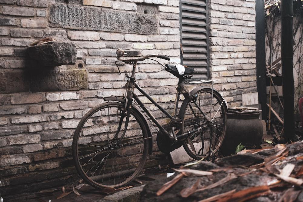 black commuter bike leaning on brown brick wall