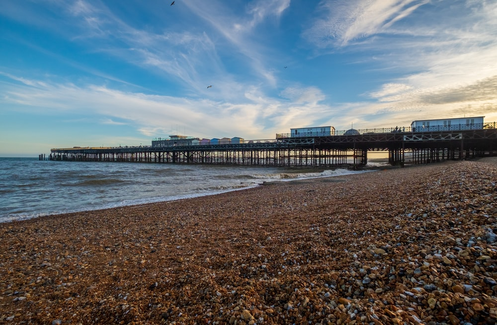 brown wooden dock on sea under blue sky during daytime