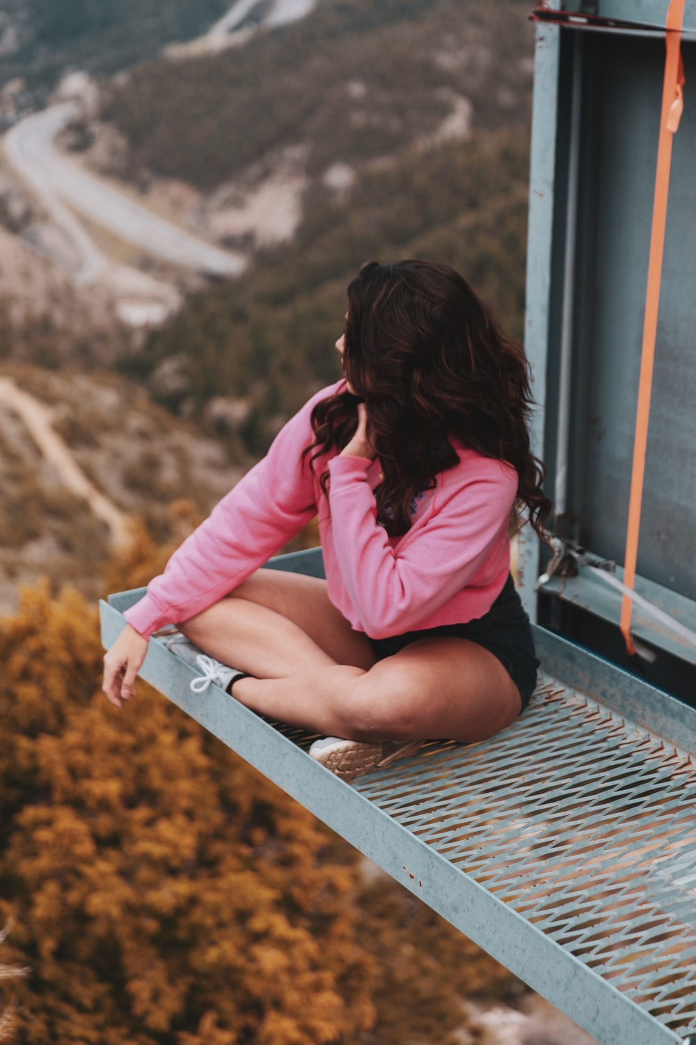 woman in pink long sleeve shirt sitting on train rail during daytime