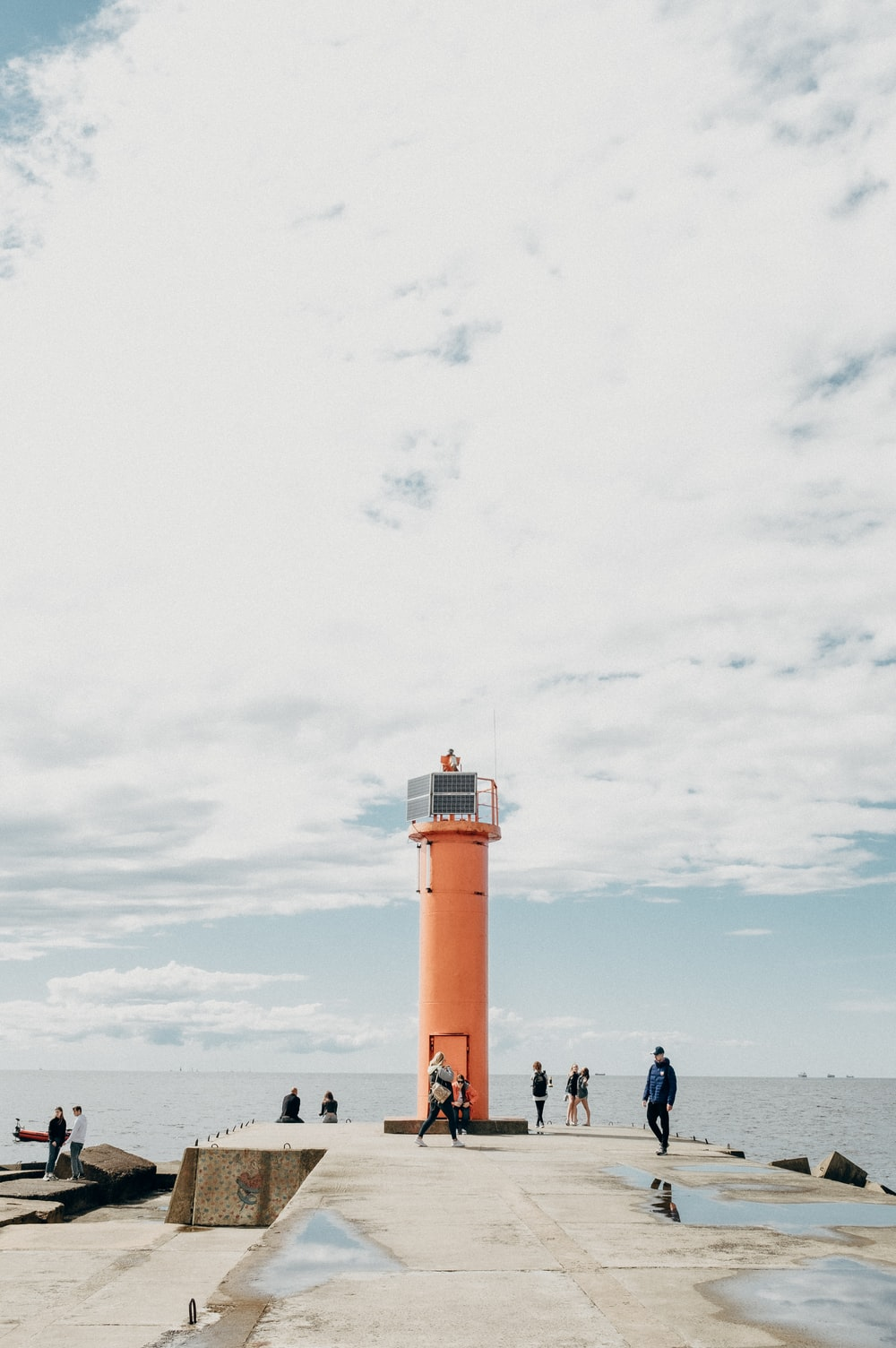 people standing near lighthouse under white clouds during daytime
