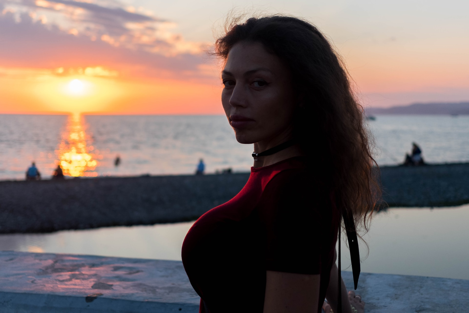woman in red long sleeve shirt standing on beach during sunset