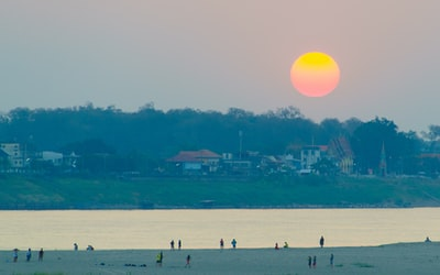 people on beach during sunset laos teams background