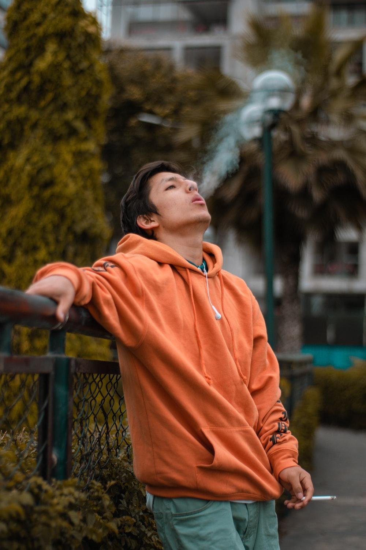 man in orange hoodie smoking