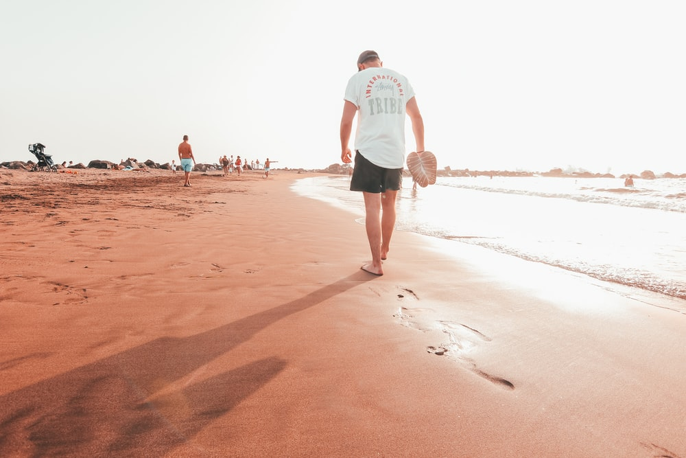 man in white t-shirt and blue shorts walking on brown sand during daytime