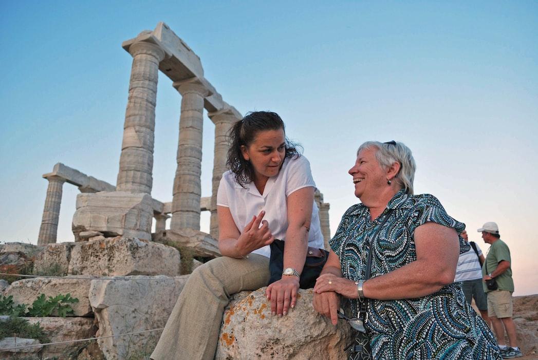 two women talk about greek temple