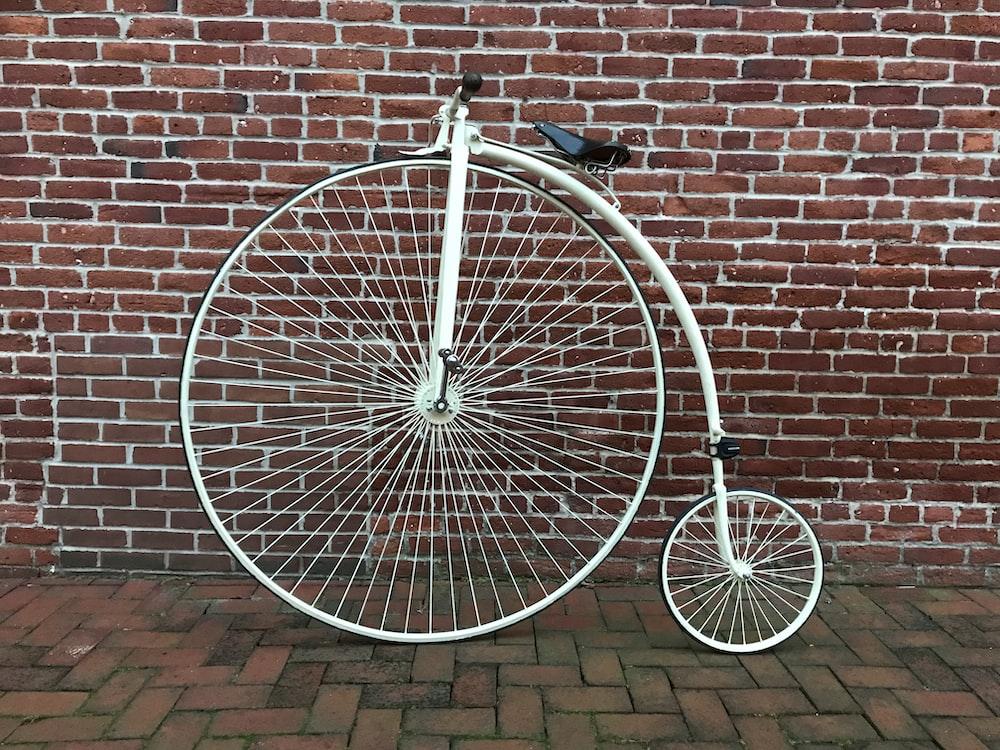 black bicycle leaning on brown brick wall
