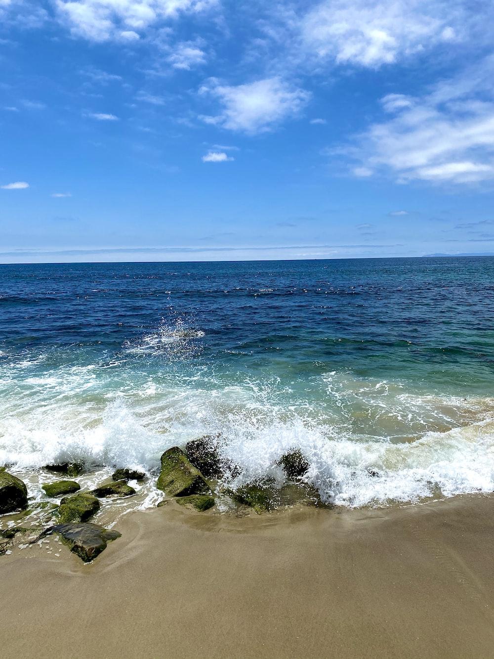 sea waves crashing on rocks under blue sky during daytime