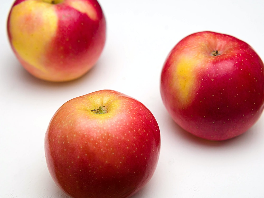 red apple fruit on white surface