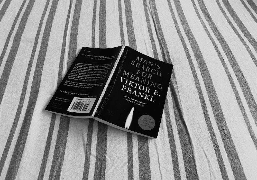 black book on gray and white striped textile