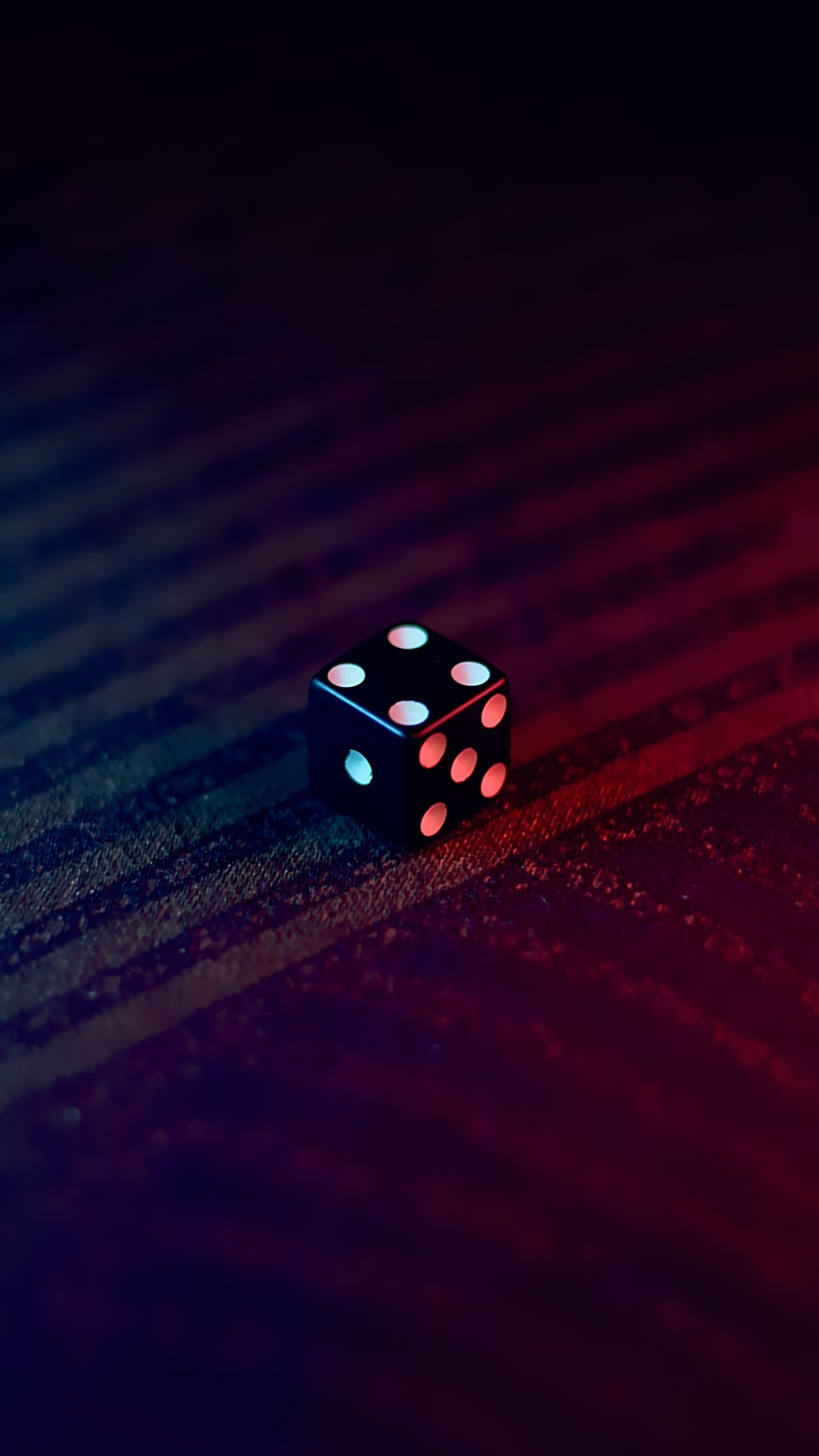 white and black dice on red textile