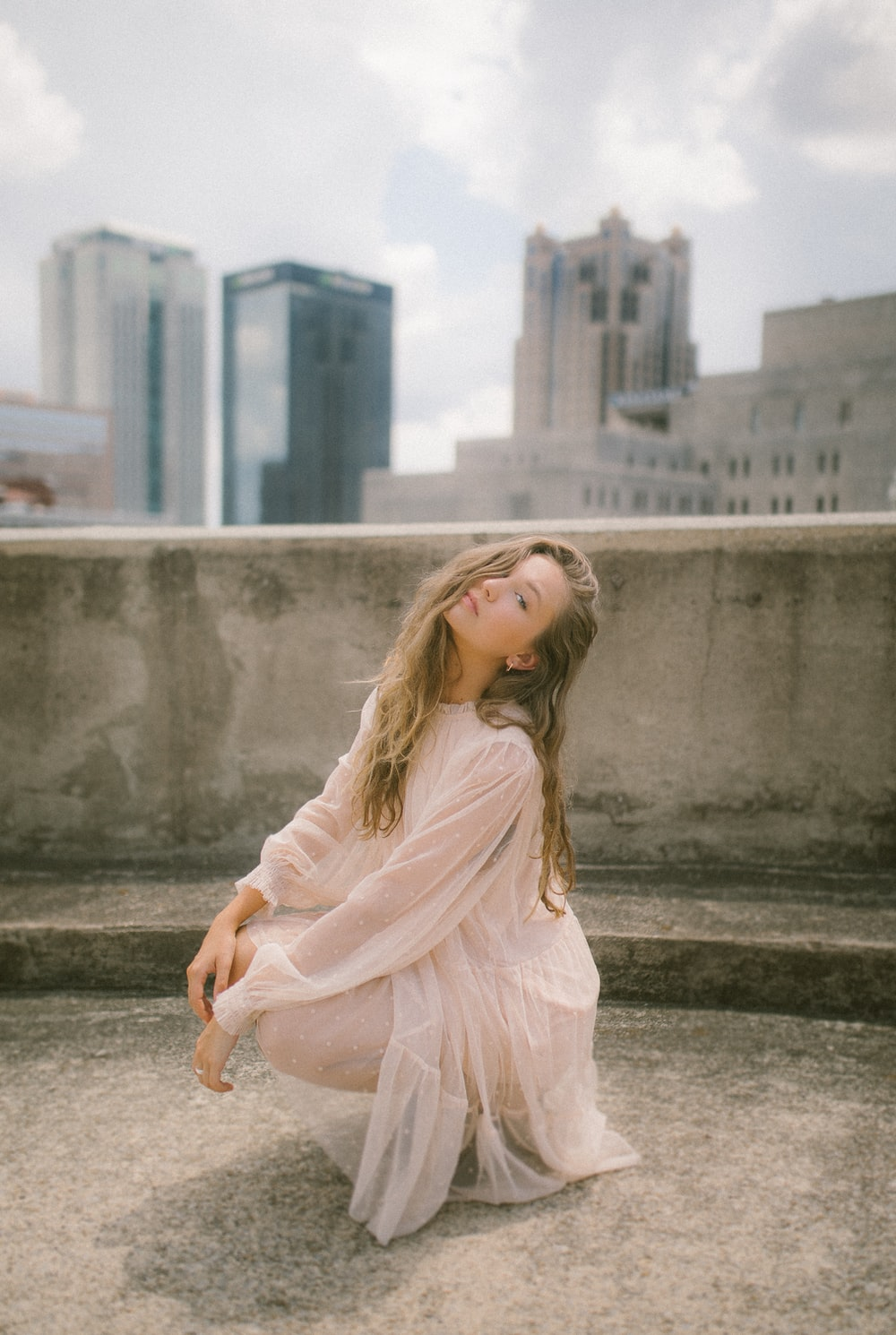 woman in pink long sleeve dress sitting on concrete bench during daytime