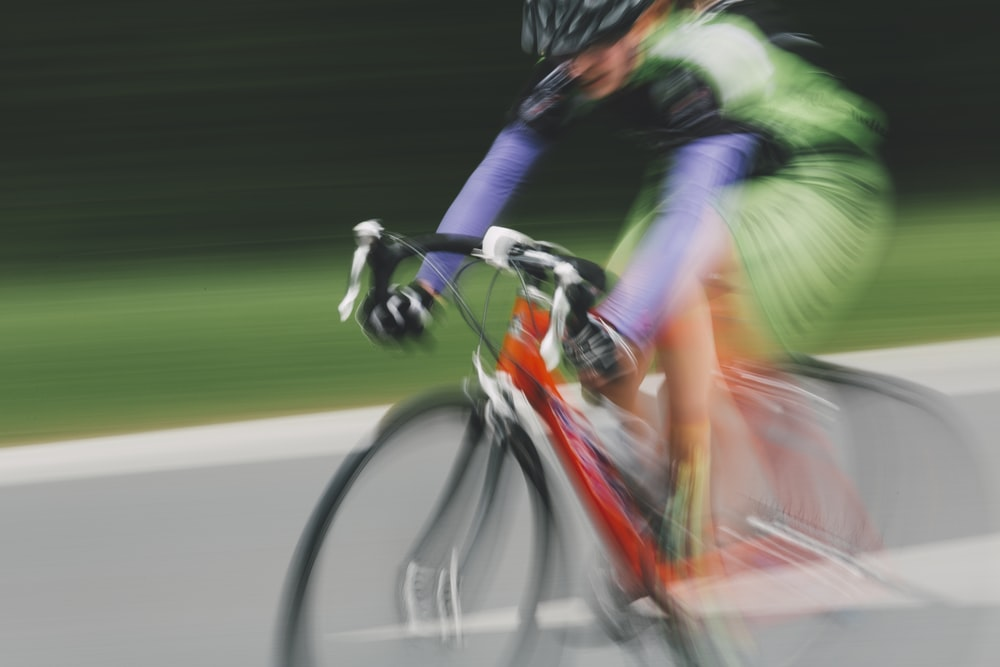 man in green and black jacket riding on bicycle