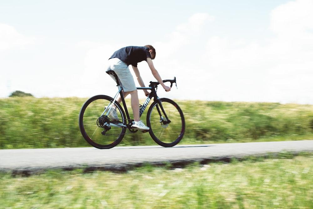 昼間に灰色のアスファルト道路で黒いマウンテンバイクに乗って黒いシャツを着た男