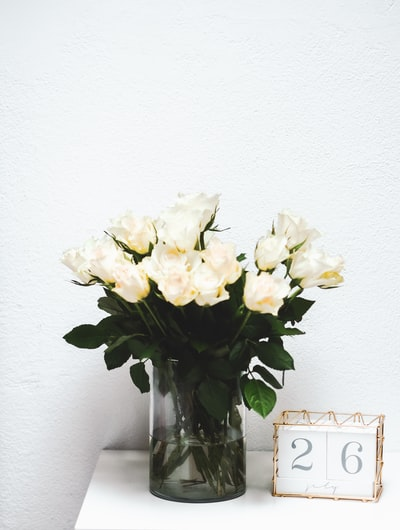 white roses in clear glass vase