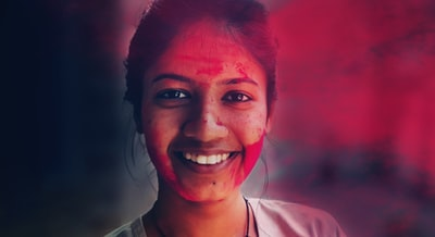 woman in white crew neck shirt smiling holi zoom background