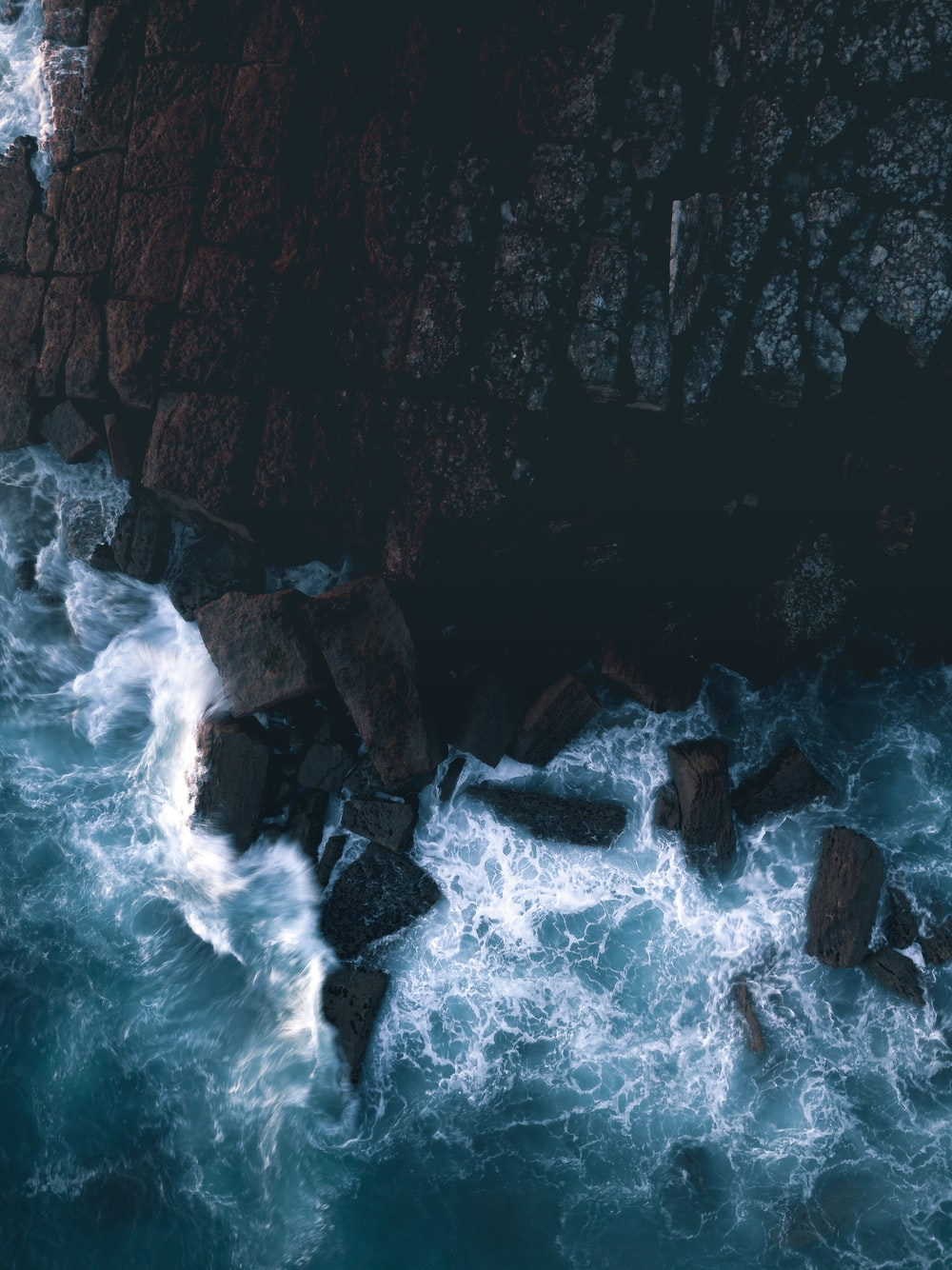 water waves hitting rocks during daytime
