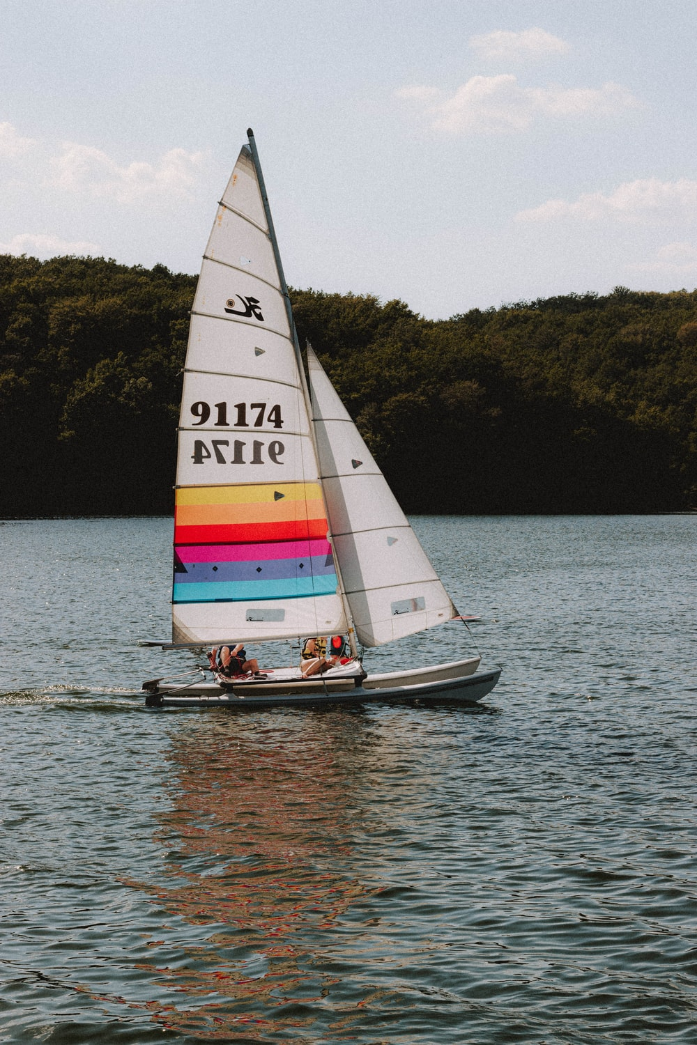 white and red sail boat on body of water during daytime