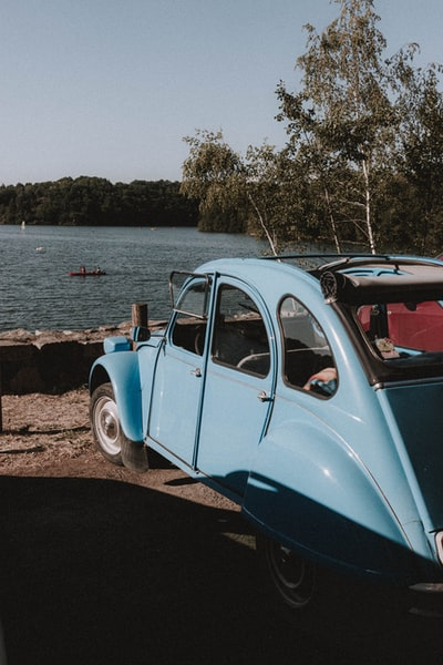 blue and white vintage car parked beside body of water during daytime