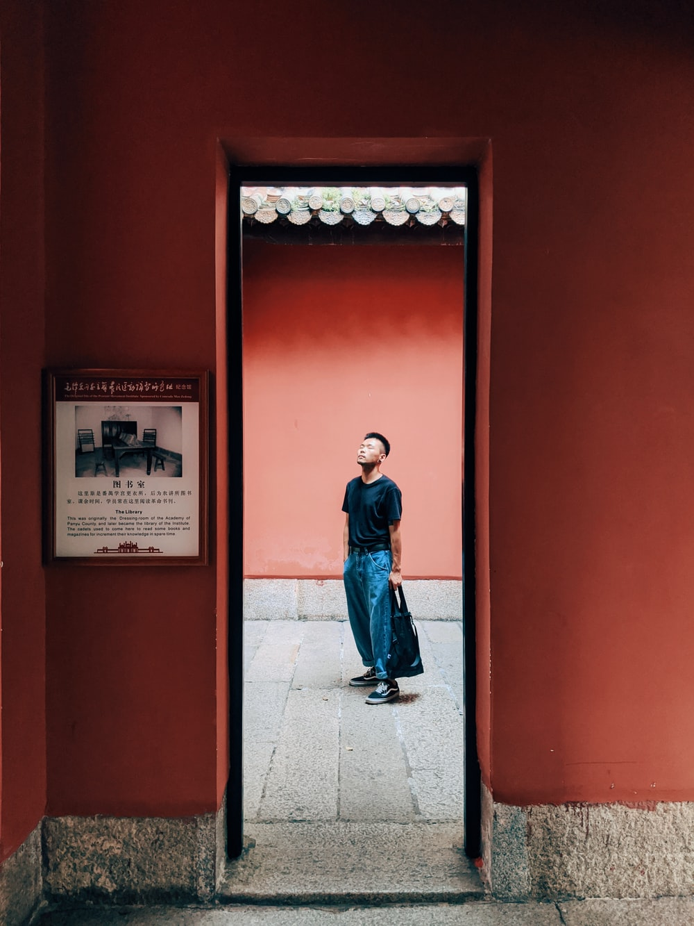 man in blue jacket and blue denim jeans standing in front of red door