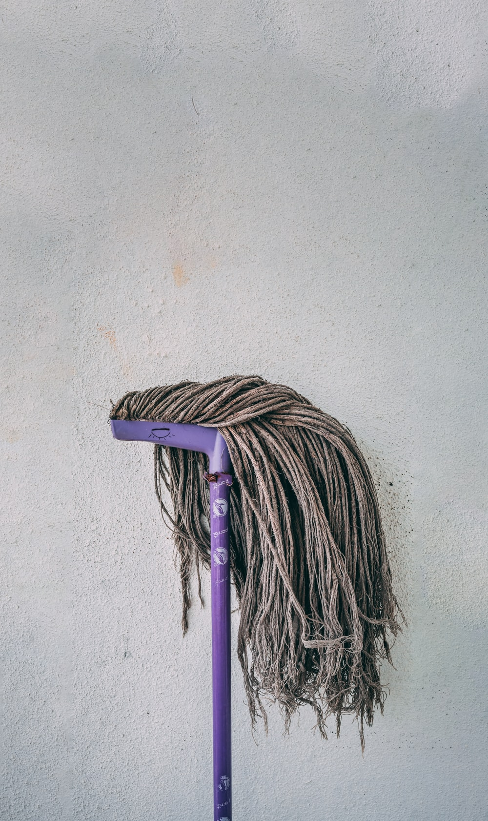 purple and white mop leaning on white wall
