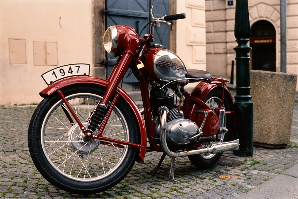 red and black standard motorcycle parked beside brown concrete building