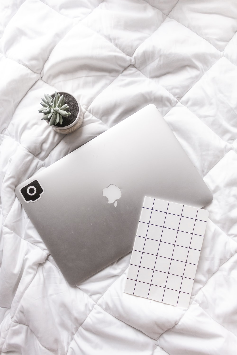 silver macbook on white and gray floral textile