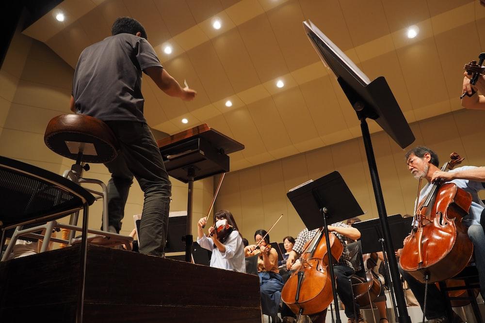 man in black t-shirt playing violin
