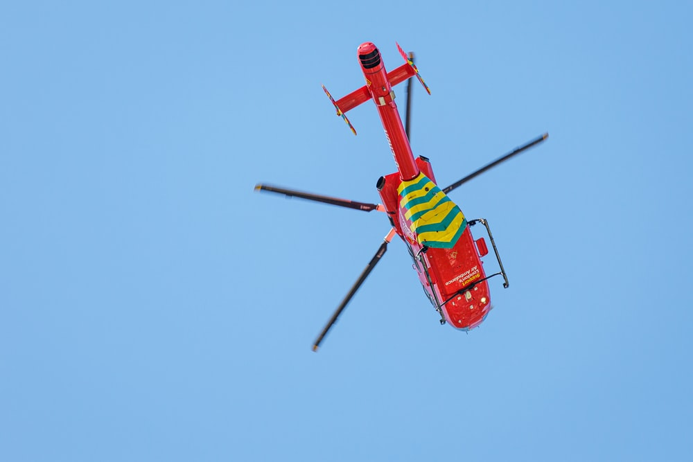 red and yellow helicopter flying in the sky