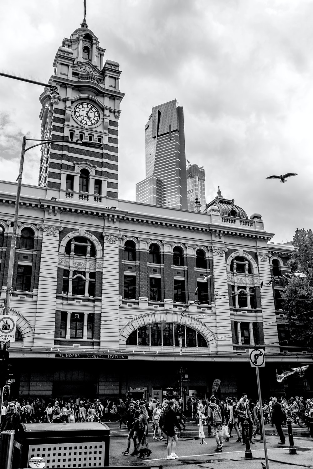 grayscale photo of concrete building with clock