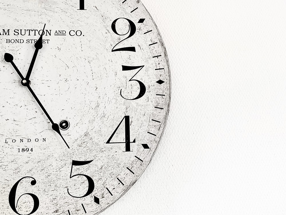 white analog wall clock at 10 00