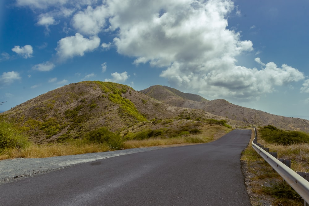 gray asphalt road near green grass field and mountain under blue sky and white clouds during