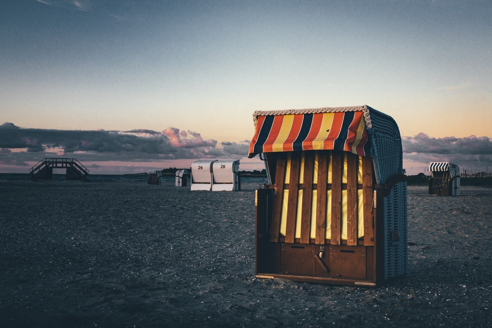 brown wooden shed on gray sand during daytime