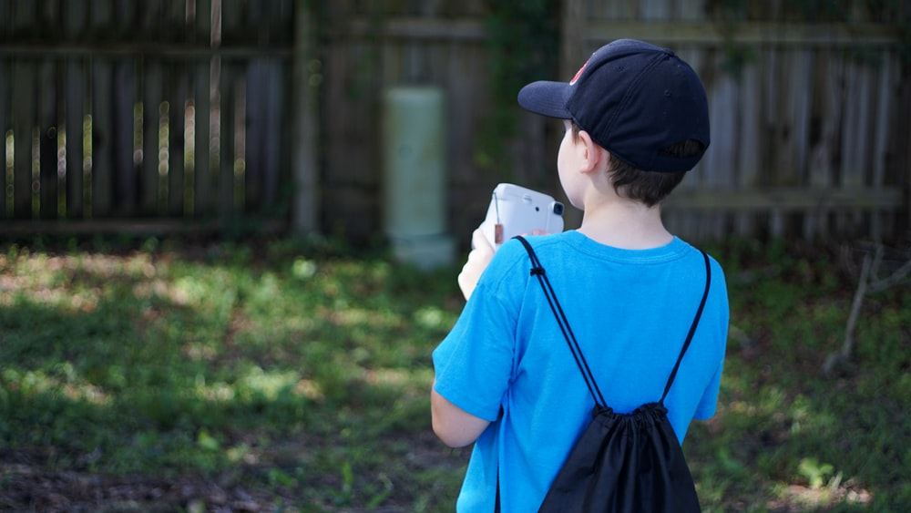 boy in blue crew neck t-shirt and black cap standing on green grass field during