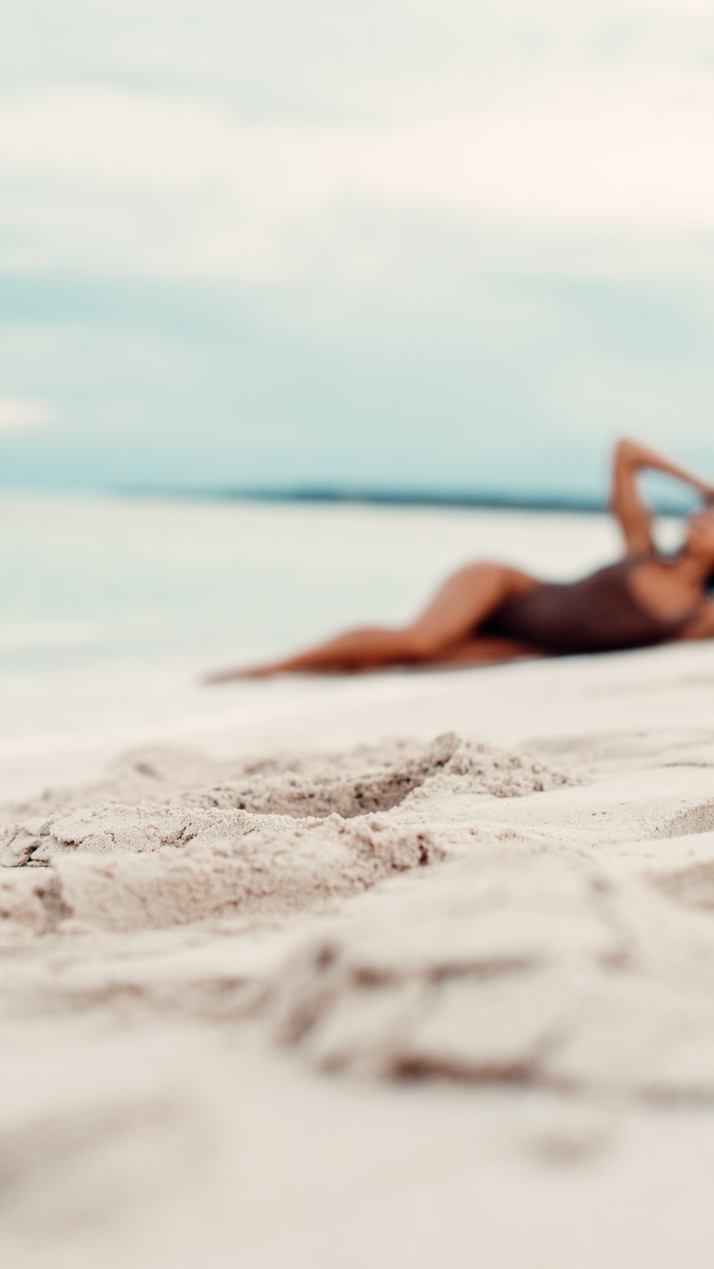 woman lying on white sand during daytime