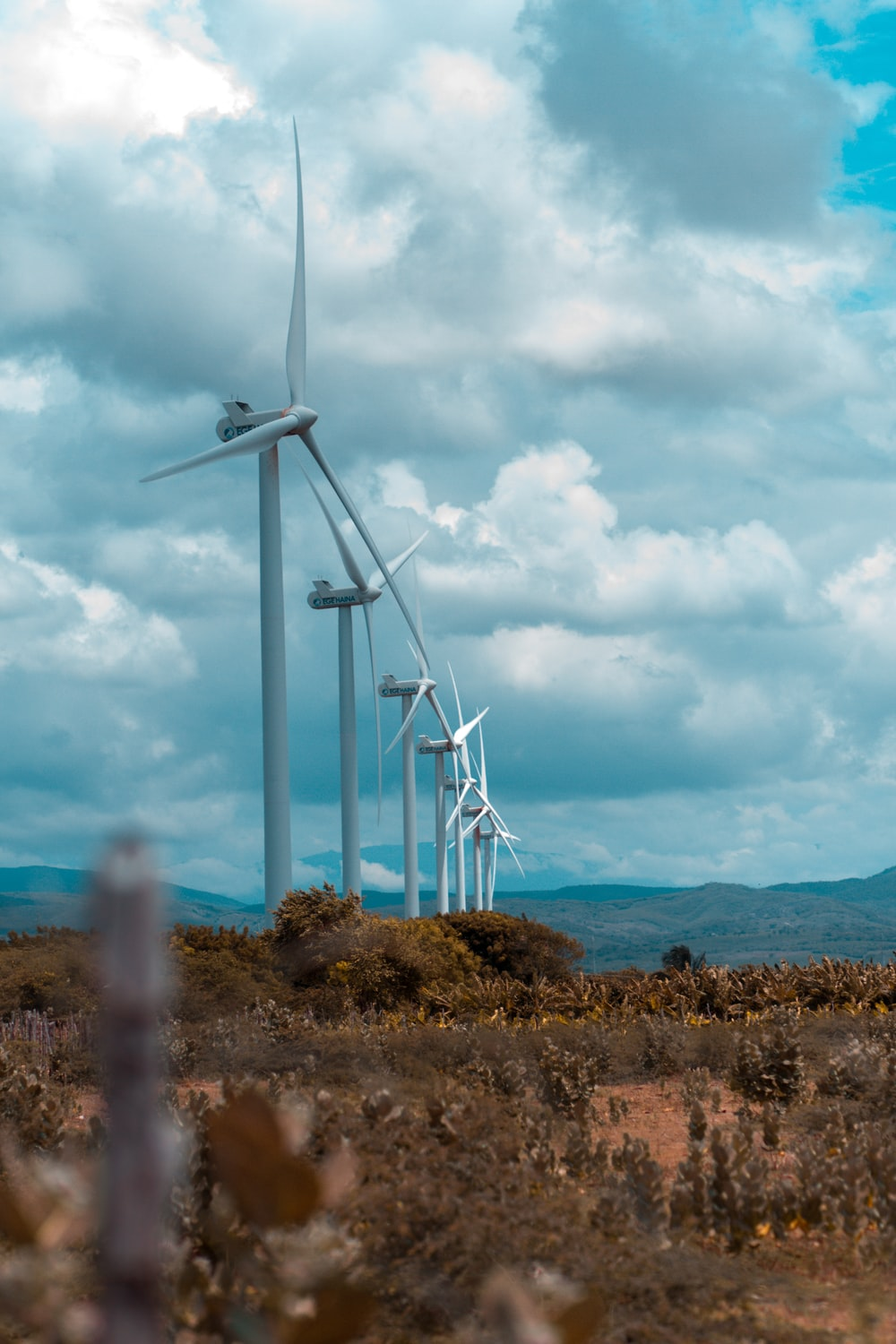 white wind turbines on green grass field under white clouds and blue sky during daytime