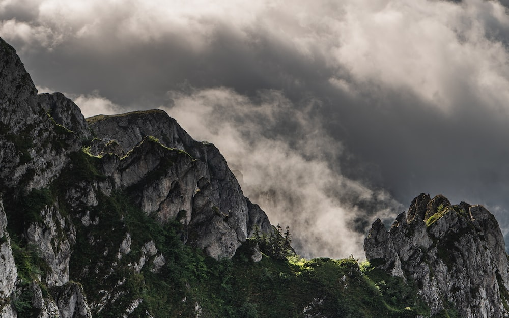 green and gray mountain under gray clouds