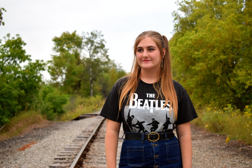 woman in black and white crew neck t-shirt and blue denim shorts standing on train