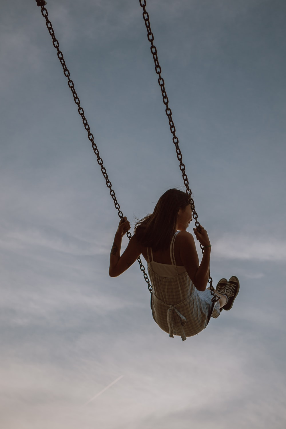 woman in white dress sitting on swing under cloudy sky during daytime