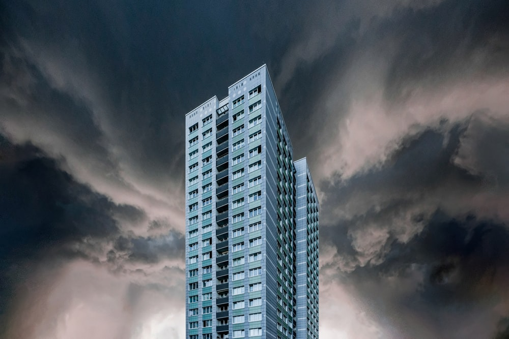 gray and white high rise building under gray clouds