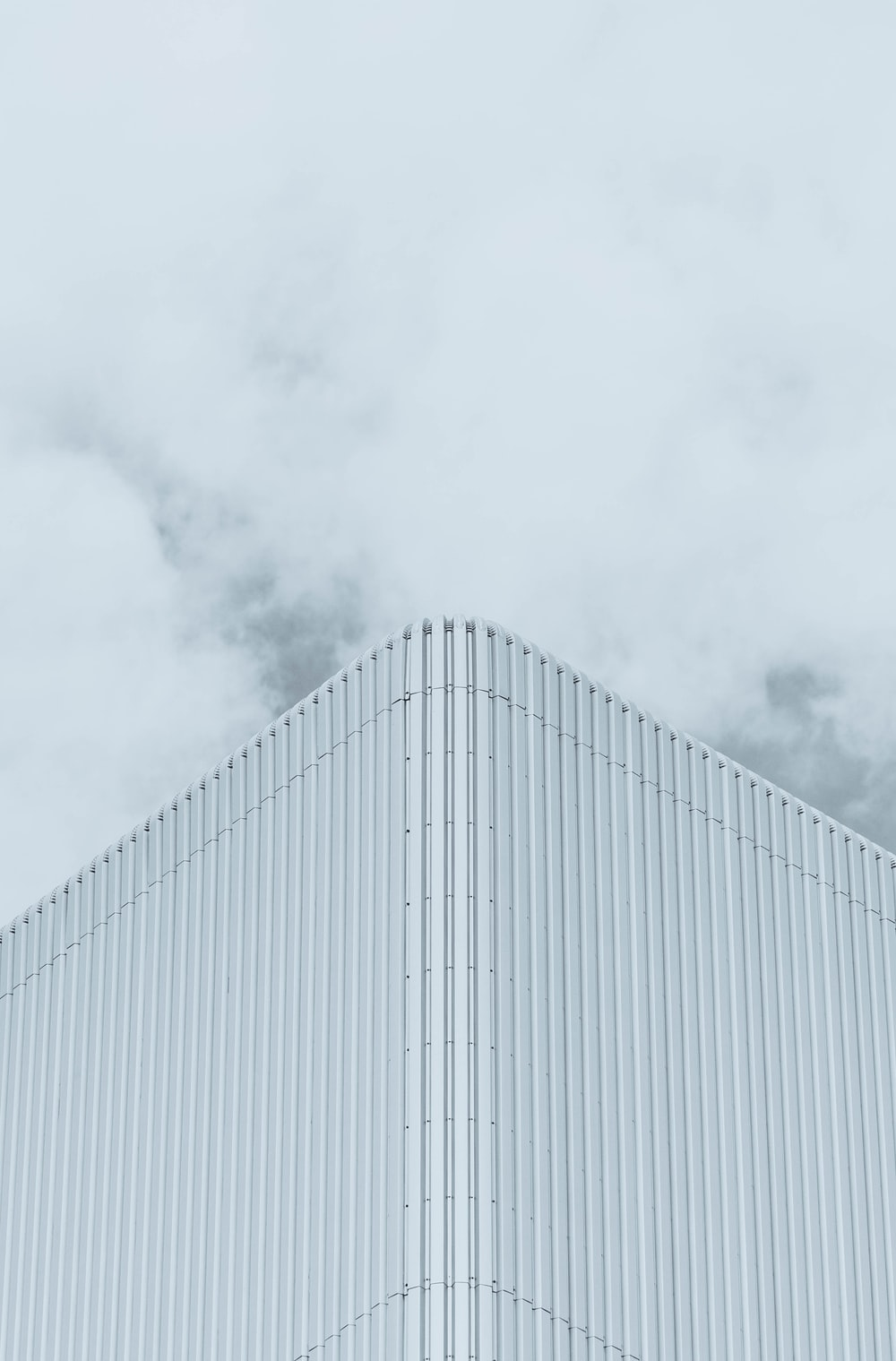 white building under white clouds