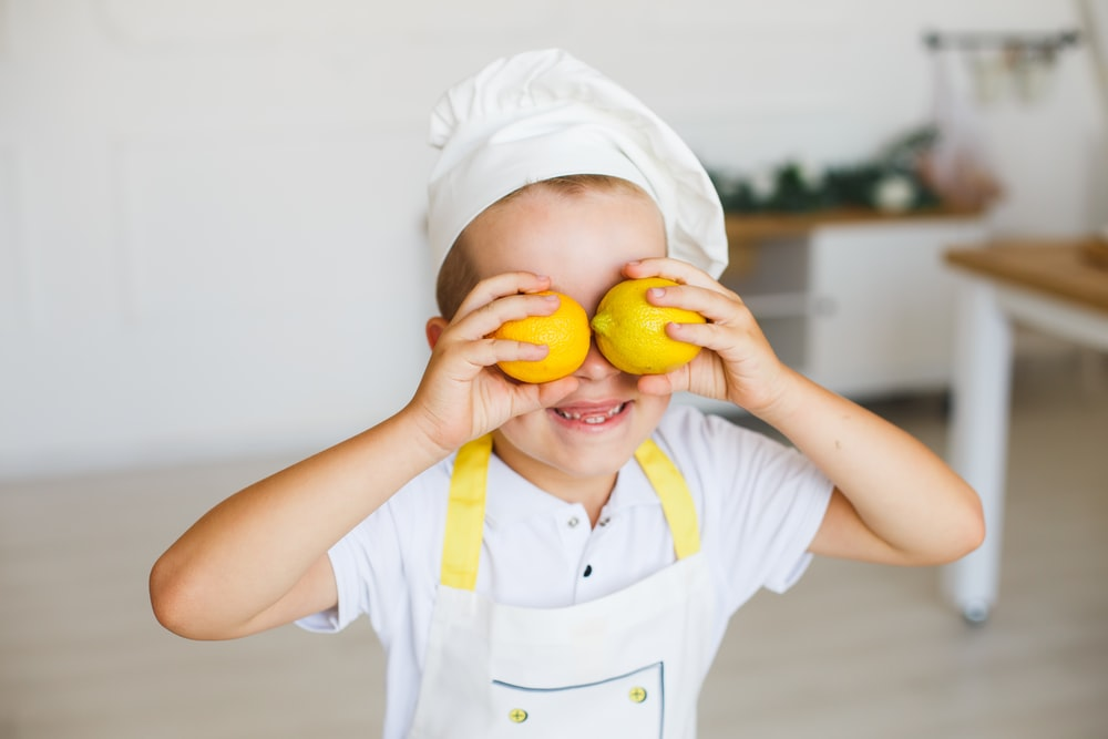 child in white polo shirt holding yellow fruit