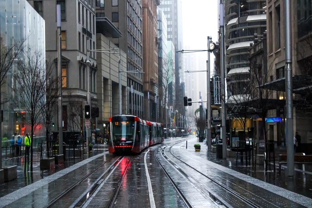 red and black tram on road between buildings during daytime