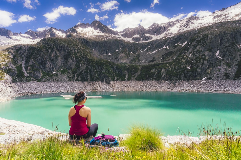 woman in black tank top sitting on green grass near lake during daytime