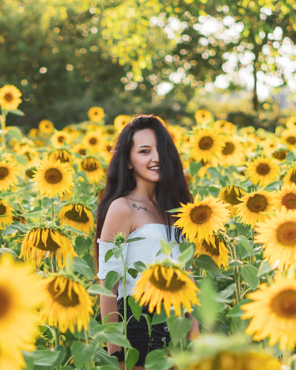 woman in white tube dress surrounded by yellow flowers