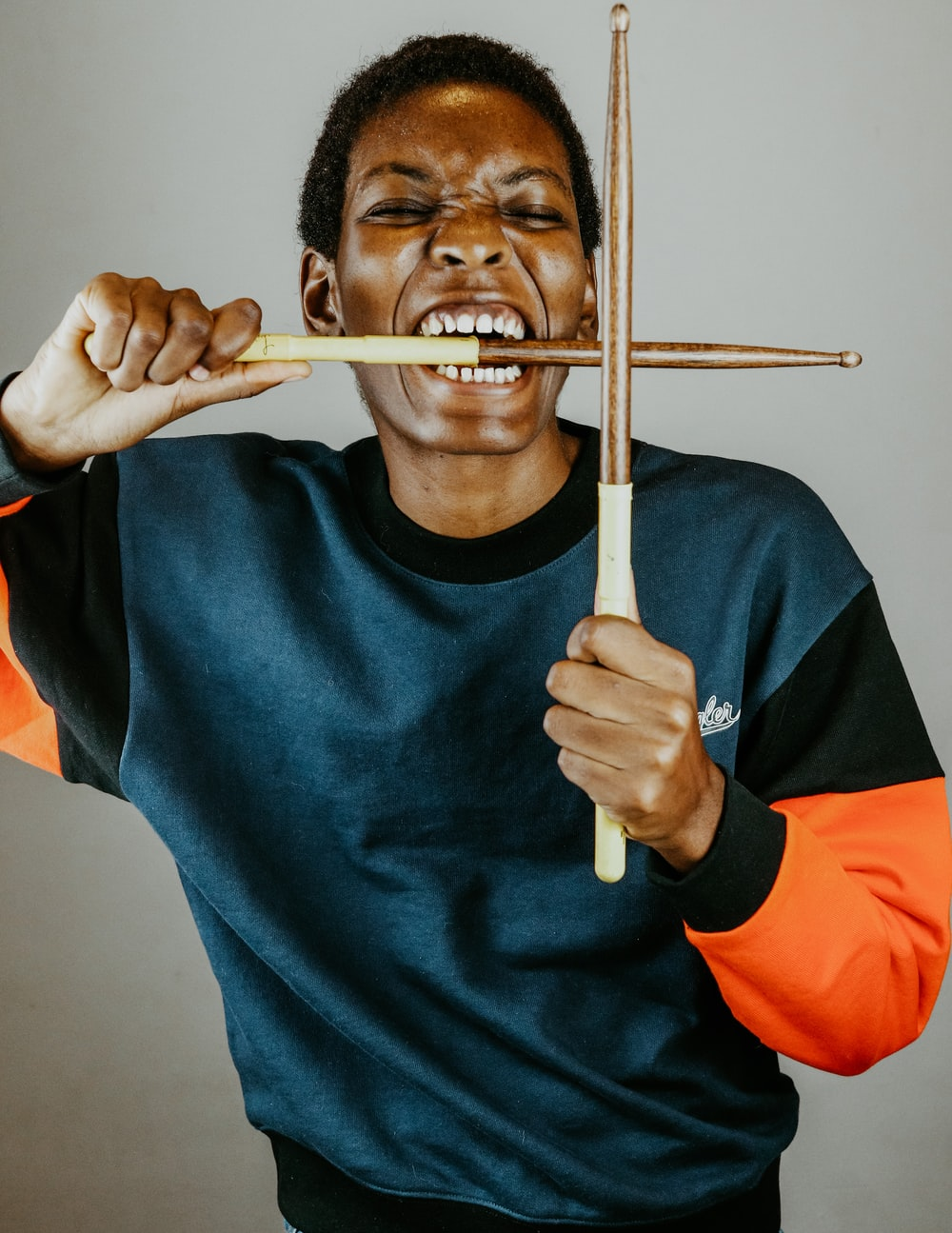 man in blue sweater holding brown wooden stick
